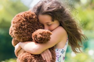 child hugging teddy bear